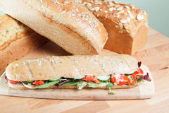 Chicken salad sandwich and loaves of bread Royalty Free Stock Images