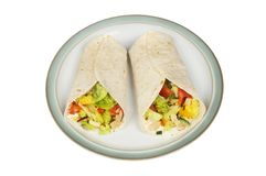 Chicken and salad wraps. Chicken and salad sandwich wraps on a plate isolated against white, top view royalty free stock images