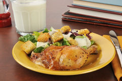 Chicken and salad after shool. A roasted chicken thigh and salad with milk as an after school snack Royalty Free Stock Image