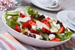 Chicken salad with strawberries, vegetables and sesame seeds. Fresh and tasty chicken salad with strawberries, vegetables and sesame seeds close up on the table Royalty Free Stock Photo