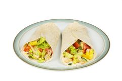 Chicken salad wraps on a plate. Chicken and salad wraps on a plate isolated against white stock photography