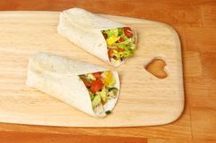 Wraps on chopping boards. Chicken and sald sandwich wraps on a wooden chopping board with a heart shaped cutout stock photos
