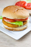Chicken Sandwich. A chicken sandwich with fresh tomato and lettuce on a white plate Royalty Free Stock Photo