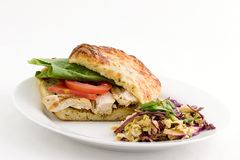 Chicken sandwich and  slaw. Grilled chicken on a cheese focaccia with dressing, romaine lettuce, tomatoes and szechuan slaw Royalty Free Stock Image