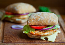 Chicken sandwiches. Two chicken sandwiches on a rustic cutting board Royalty Free Stock Photo