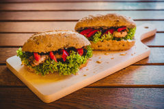 Chicken sandwiches. On a wooden plate and table Stock Images