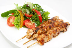 Chicken Satay. Delicious chicken satay skewers with fresh green salad royalty free stock photos