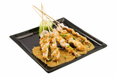 Chicken satay. Black plate with chicken satay on white stock photos