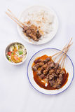 Chicken satay with delicious peanut sauce served with white rice and vegetables. On white background Stock Photography