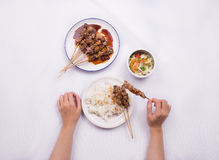 Chicken satay with delicious peanut sauce served with white rice and vegetables. With hand Stock Photo