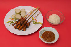 Chicken Satay Indonesian Cuisine with rice cake  on red Stock Photo
