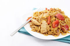 Chicken Satay noodles. Plate of chicken satay noodles with red peppers and onions and a fork stock images