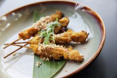 Chicken satay, sate ayam and lontong with peanut sauce. In close up stock photo