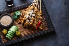 Chicken Satay or Sate Ayam - Malaysian famous food. Is a dish of seasoned, skewered and grilled meat, served with a. Peanut sauce. Darkphoto. Top view copyspace stock image