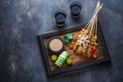 Chicken Satay or Sate Ayam - Malaysian famous food. Is a dish of seasoned, skewered and grilled meat, served with a. Peanut sauce. Darkphoto. Top view copyspace royalty free stock photo