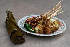 Chicken satay street food dish complete with brown sweet peanut sauce, rice cake slices and fresh cucumber slices served using royalty free stock image