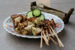 Chicken satay street food dish complete with brown sweet peanut sauce, rice cake slices and fresh cucumber slices served using royalty free stock images