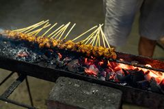 Chicken sate on the grill shelf with fire on charcoal until well done. Ones of kind indonesian streetfood stock photography