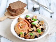 Chicken sausages with the grilled mushrooms and basil on a white wooden table Royalty Free Stock Image