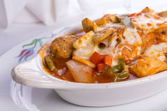 Chicken Saute Baked in Oven in Oval Dish Cheese melted on top of Royalty Free Stock Image