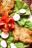 Chicken schnitzel. S on a vegetables background stock image