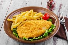 Chicken schnitzel. Breaded chicken schnitzel fries potatoes Stock Photography
