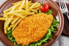 Chicken schnitzel. Breaded chicken schnitzel fries potatoes Royalty Free Stock Photos