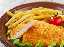 Chicken schnitzel. Breaded chicken schnitzel fries potatoes Stock Images