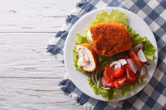 Chicken schnitzel cordon bleu and a salad. Horizontal top view Stock Photo