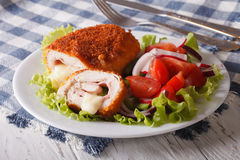 Chicken schnitzel cordon bleu and salad on a plate close-up. hor Stock Image
