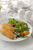 Chicken schnitzel garnish of arugula tomatoes Royalty Free Stock Photography