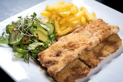 Chicken schnitzel, served with fries and salad. Natural wooden background. royalty free stock photos