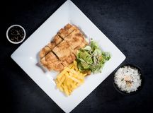 Chicken schnitzel, served with fries and salad. Natural wooden background. stock image