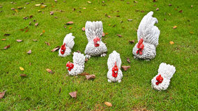 Chicken sculpture. Family on the grass floor Stock Photography