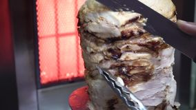 Chicken shawarma on a spit. Cook cuts shawarma chicken on skewer stock footage