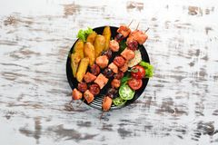 Chicken shish kebab with potatoes and vegetables on a white wooden background. Meat. Top view. Free copy space stock image