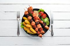 Chicken shish kebab with potatoes and vegetables on a white wooden background. Meat. Top view. Free copy space royalty free stock photography