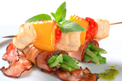 Chicken skewer and bacon-wrapped green beans stock image