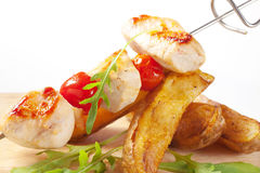 Chicken skewer and potato wedges Stock Photos