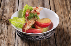 Chicken skewer and roasted apple Royalty Free Stock Image