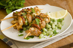 Chicken skewers. Chicken and chorizo skewers with broad beans and mint Royalty Free Stock Image