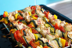 Chicken skewers with bacon and vegetables on a tray. Chicken skewers with bacon, tomatoes, cucumbers, onions and bell peppers on a tray Royalty Free Stock Image