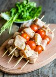 Chicken skewers with cherry tomatoes. Spiced chicken skewers with cherry tomatoes and greens Royalty Free Stock Photo