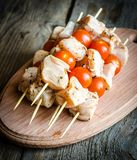Chicken skewers with cherry tomatoes. Spiced chicken skewers with cherry tomatoes and greens Royalty Free Stock Images