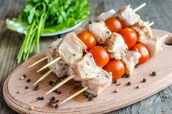 Chicken skewers with cherry tomatoes. Spiced chicken skewers with cherry tomatoes and greens Stock Images