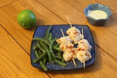 Chicken skewers with dipping sauce and green beans Stock Image