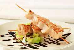 Chicken skewers. Garnished with balsamic vinegar stock image