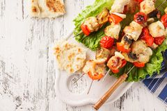Chicken skewers with mushrooms, vegetables and fresh lettuce royalty free stock images