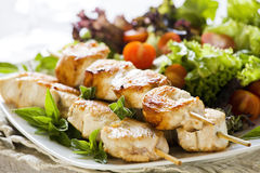 Chicken Skewers with Salad. Close up photograph of three chicken skewers served with salad Stock Photos