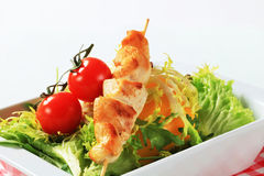 Chicken skewers and salad greens Royalty Free Stock Images
